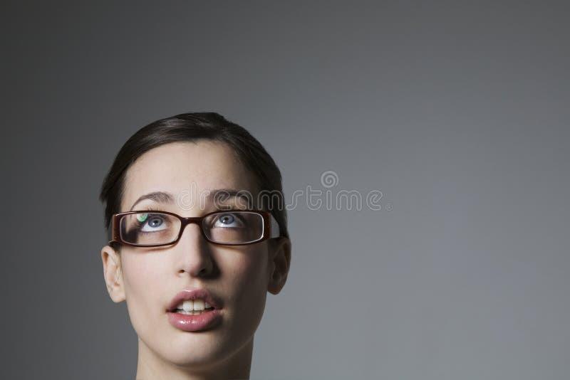 Gafas que llevan femeninas jovenes que miran hacia arriba fotografía de archivo