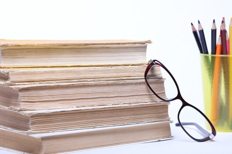 Gafas que mienten en el libro viejo Lápices en un vidrio fotos de archivo