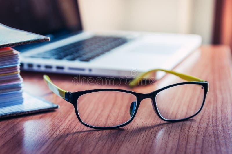Gafas y ordenador portátil en el escritorio imagen de archivo libre de regalías