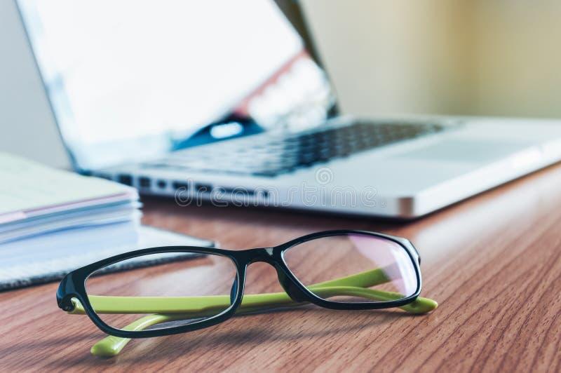 Gafas y ordenador portátil en el escritorio fotos de archivo
