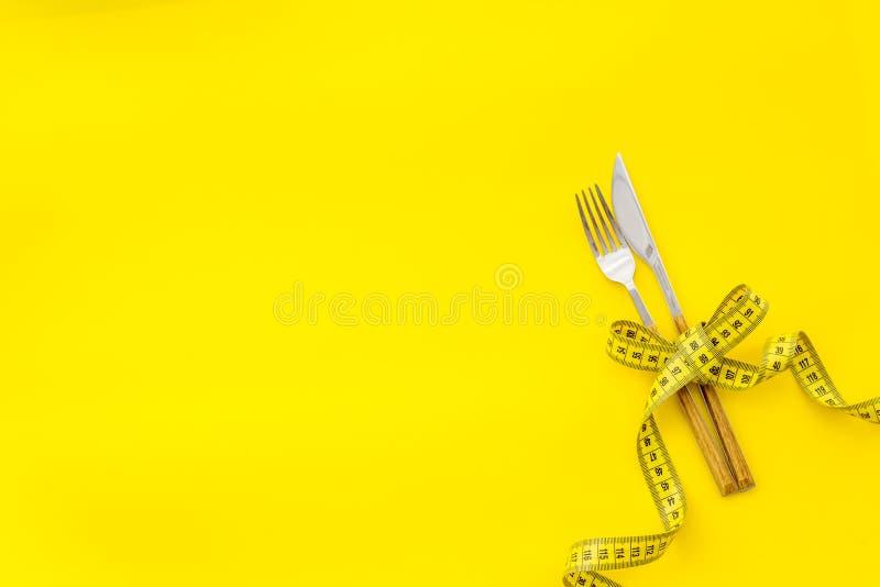 Gaffel och kniv nära att mäta upp bandet på gul åtlöje för bästa sikt för bakgrund arkivbild