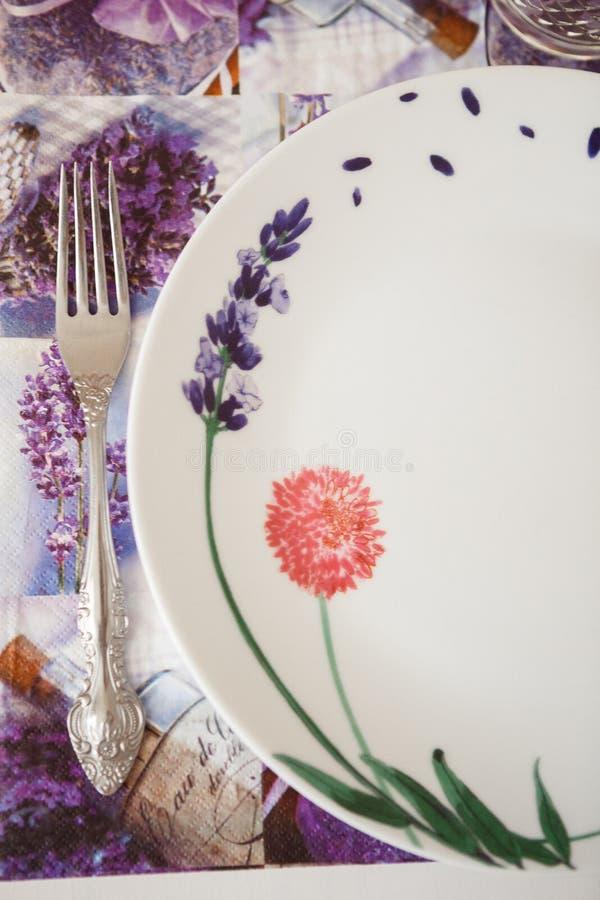 Gaffel och platta på en servett med purpurfärgade blommor arkivfoto