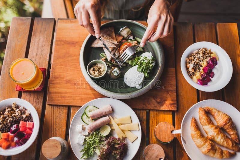 Gaffeln för kvinnahandinnehavet, baktalar och äter frukosten royaltyfria foton