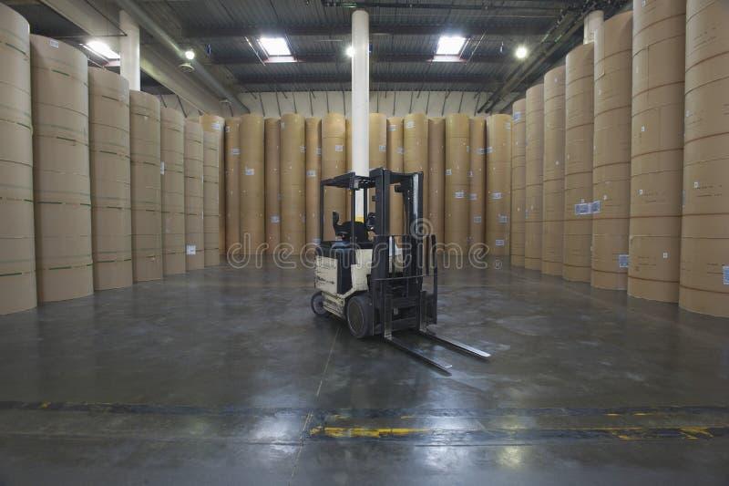 Gaffeltruck och enorma Rolls av papper i fabrik royaltyfri foto