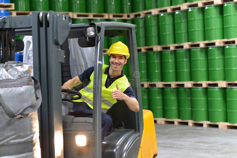 Gaffeltruckchaufför i en logistikkorridor av ett kemiskt lager arkivbilder