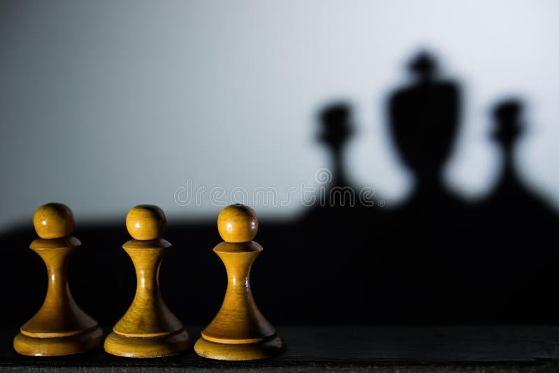 Gage des échecs trois avec on moulant une ombre de morceau de roi dans le concept foncé de la force et des aspirations image stock