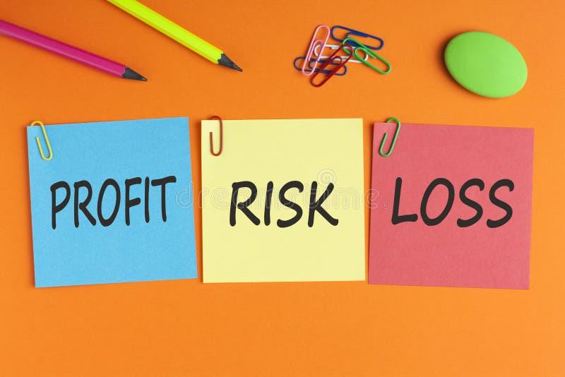 Gagna, risken och förlust som är skriftliga på anmärkningar arkivfoto