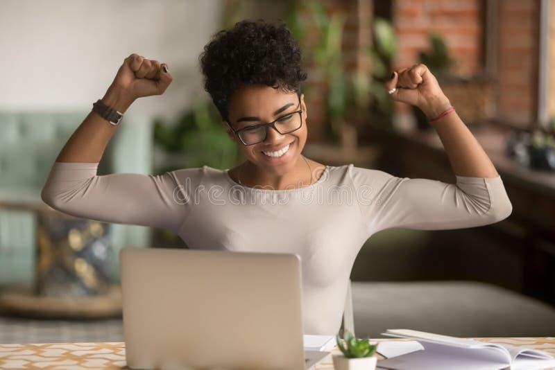 Gagnant africain enthousiaste de sentiment de femme se réjouissant la victoire en ligne sur l'ordinateur portable photographie stock