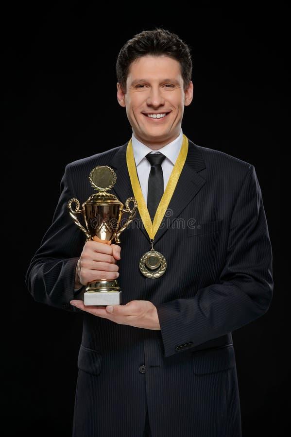 Gagnant d'affaires. Homme d'affaires heureux tenant un trophée tandis que standi photo stock