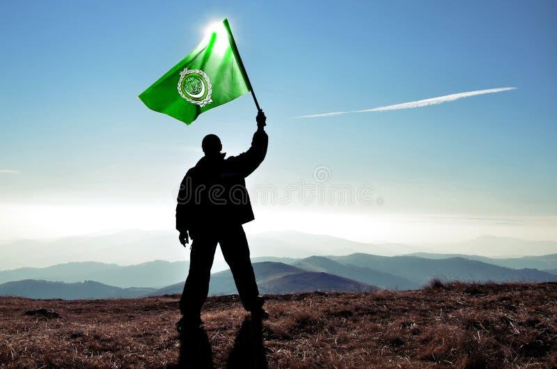 Gagnant d'homme ondulant le drapeau de ligue arabe photos stock