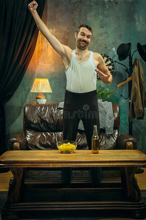 gagnant Mains mobiles accablées d'homme gai tout en célébrant la victoire d'une équipe de football préférée photos stock