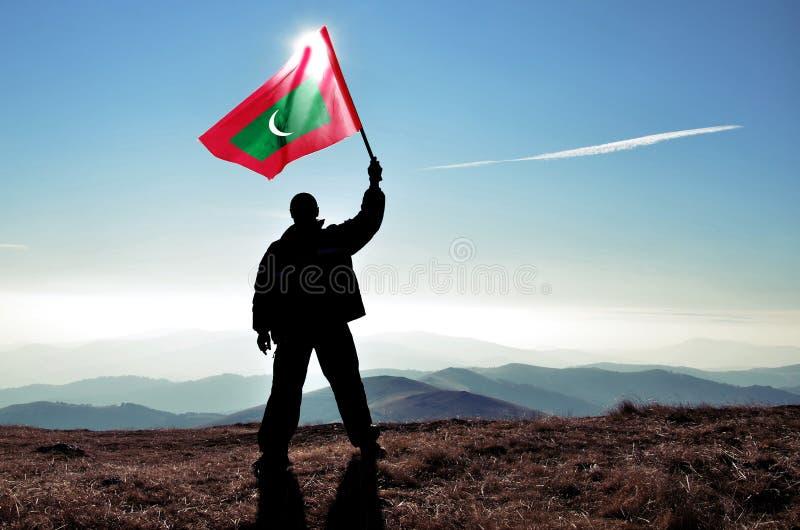 Gagnant réussi d'homme de silhouette ondulant le drapeau des Maldives sur la montagne images libres de droits