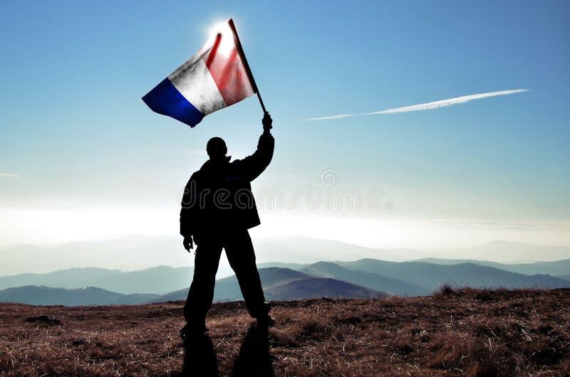 Gagnant réussi d'homme de silhouette ondulant le drapeau français sur la montagne image libre de droits