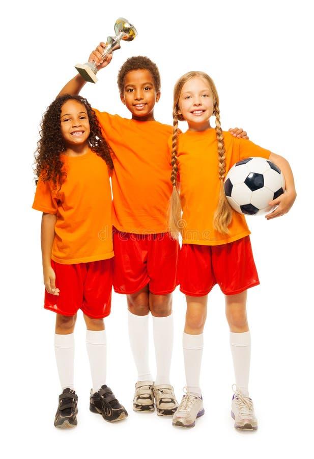 Gagnants heureux d'enfants de jeu de football avec la tasse professionnelle photos libres de droits