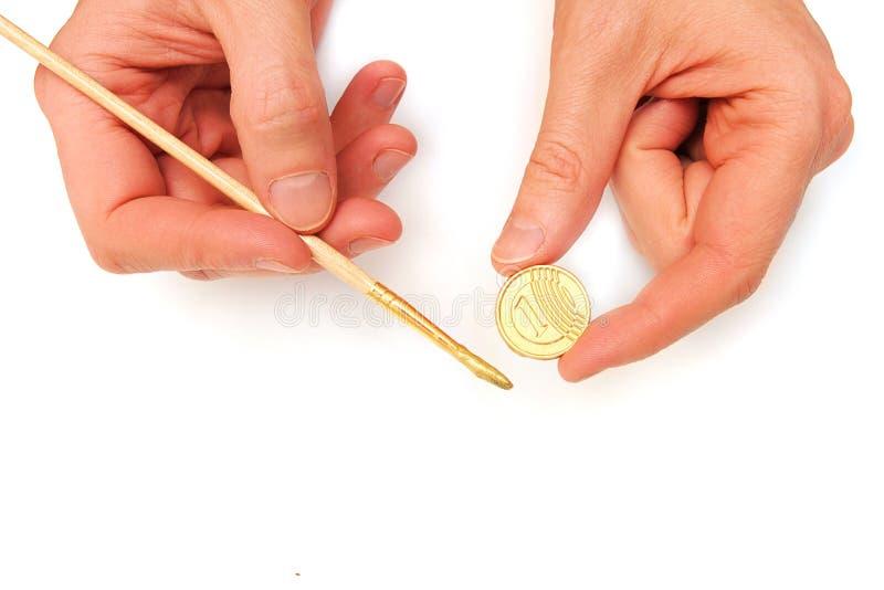 Gagner l'argent. Pièce d'or et un balai dans des mains mâles photo libre de droits