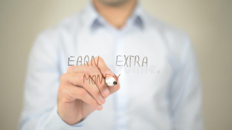 Gagnez l'argent supplémentaire, écriture d'homme sur l'écran transparent photographie stock libre de droits