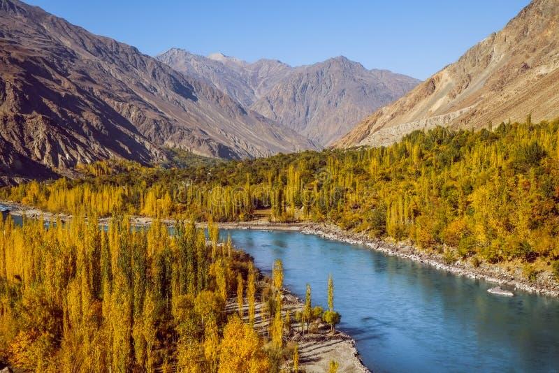 Gahkuch en el río de la demostración del otoño atraviesa el bosque colorido y rodeado por las montañas en gama del karakoram imagenes de archivo