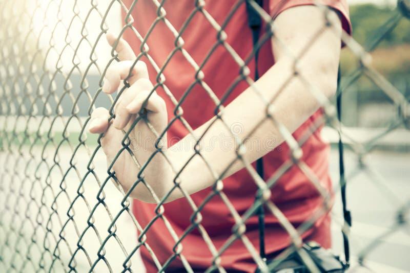 Gaiola de travamento da malha da mão O prisioneiro quer a liberdade imagens de stock