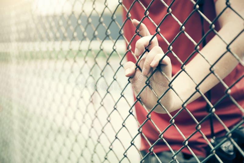 Gaiola de travamento da malha da mão O prisioneiro quer a liberdade imagem de stock