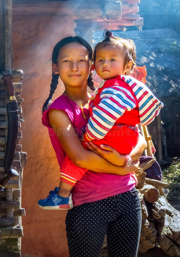 Big girl with braids holding little boy, Nepal. Gairi Pangma, Sankhuwasabha District, Nepal - 11/18/2017 : Big girl with braids holding little boy royalty free stock photography