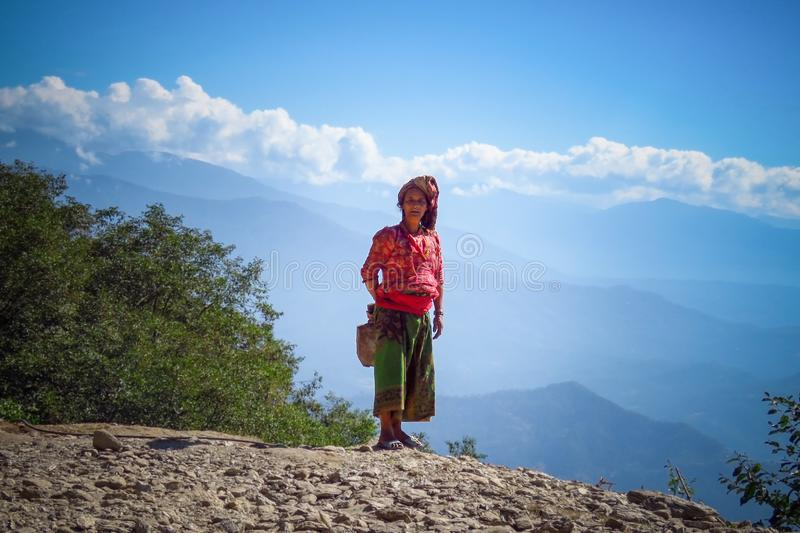 Nepalese woman in traditional clothes against the blue sky in the mountain village Gairi Pangma, Nepal. Gairi Pangma, Sankhuwasabha District, Nepal - 11/19/2017 stock photos