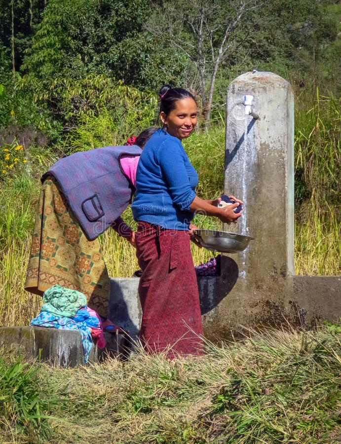 Women washing clothes at a public water tap in a small mountain village, Nepal. Gairi Pangma, Sankhuwasabha District, Nepal - 11/19/2017 : Nepalese woman washing royalty free stock images