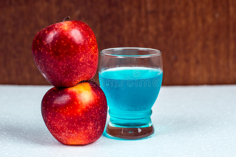Gala apple and a glass of blue mocktail at party night. stock photography