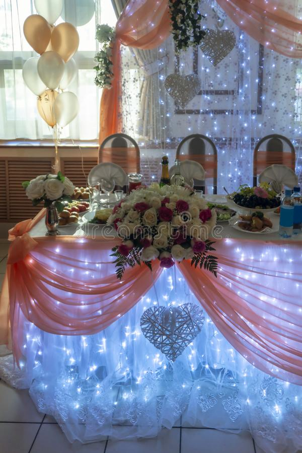 Gala wedding table decorated with balloons, lights and other decorations. Wedding table with flowers and lights decorations, champagne and food on festive table stock image