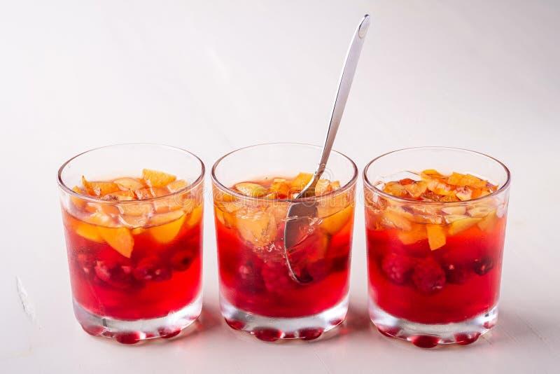 Galaretowy deser z owoc morelową malinką w trzy pije szkłach z pojedynczego łyżkowego żółtego czerwonego lata białym tłem w rzędz zdjęcie royalty free