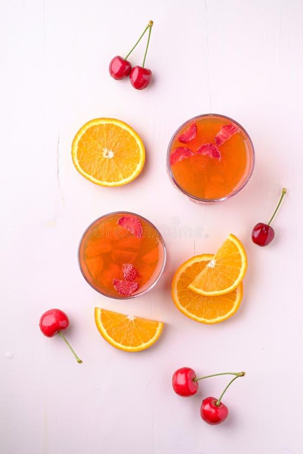 Galaretowy deser z truskawkami w napoju szkle z czereśniowymi jagodami i pomarańcze pokrajać niedalekiego odgórnego widok obraz stock