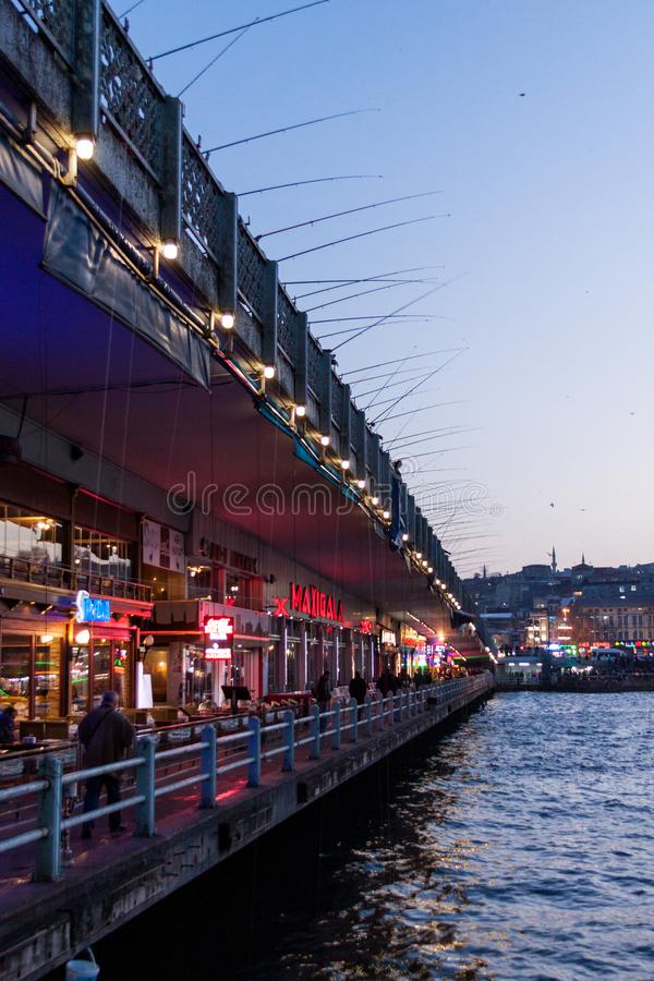 The Galata Bridge at Sunset. The local continue to fish off the Galata Bridge at sunset in Istanbul, Turkey stock images