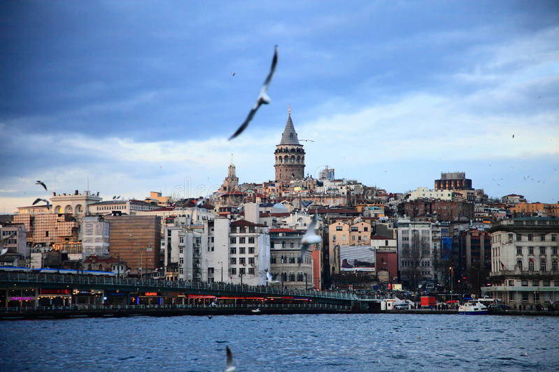 Galata Tower In Istanbul. Galata Tower at center of image. Also Galata Bridge is in the image. Birds are flying in blue sky royalty free stock image