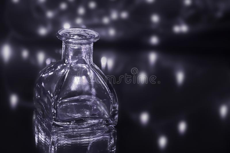 Galaxy away. Empty, small and square glass bottle placed on mirror with lights in blurred dark background.Object, dark and moody still life abstract.Fine art royalty free stock photos