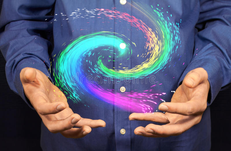 Galaxy. A colorful galaxy floating above two hands stock photo