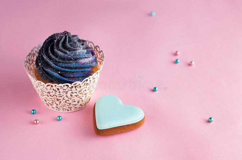 Galaxy cupcake on pink background with copyspace royalty free stock photo