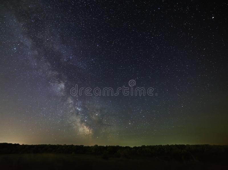 Galaxy Milky Way in the night sky against background of dense. Galaxy Milky Way in the night sky against a background of dense forest royalty free stock photo