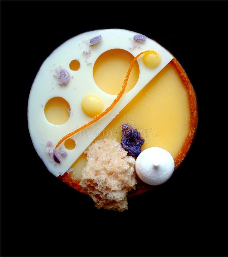 Galdéria alaranjada brilhante com merengues, esponja da micro-ondas e chocolate branco no fundo preto fotografia de stock