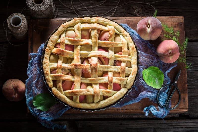 Galdéria caseiro e deliciosa com os pêssegos no pano azul fotos de stock
