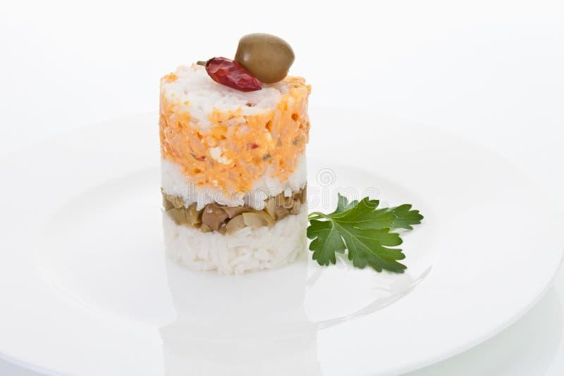 Galdéria do arroz decorada com azeitona, o pimentão vermelho e salsa italiana imagens de stock royalty free
