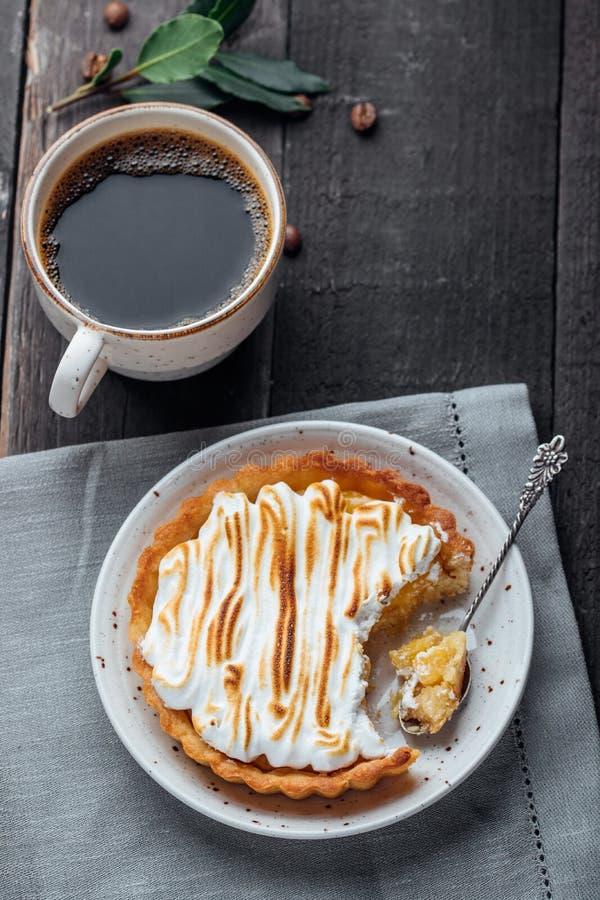 Galdéria feito à mão, tartlet com coalho de limão e merengue e xícara de café em um fundo de madeira preto Foco seletivo fotografia de stock royalty free