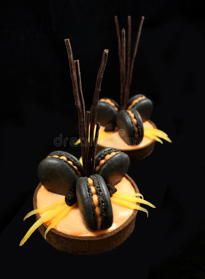 Galdérias alaranjadas do chocolate com macarons franceses pretos e caqui no fundo preto foto de stock royalty free