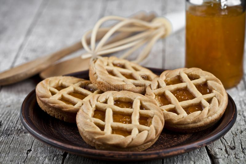 Galdérias cozidas frescas com o doce do doce de fruta ou do abricó que enche-se e na placa e no utensílio cerâmicos da padaria da imagens de stock