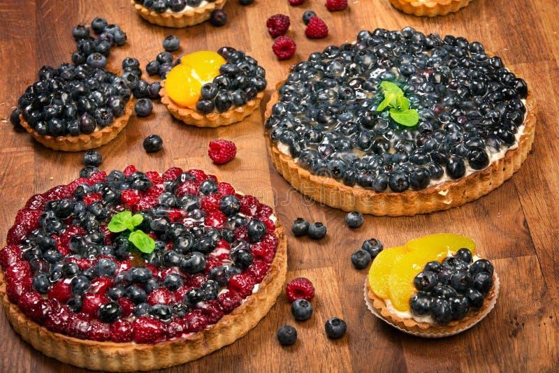 Galdérias doces com frutos, framboesas, mirtilos e pêssegos em um fundo de madeira fotografia de stock royalty free