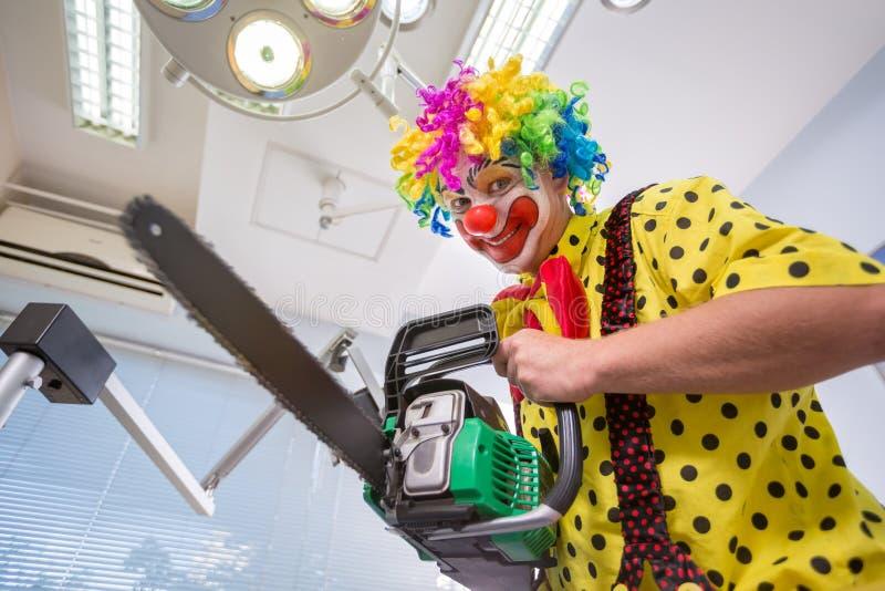 Galen clown med chainsawen i tand- klinik royaltyfri bild
