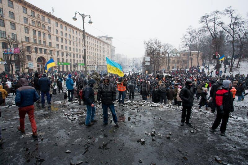 Galen folkmassa av personer som protesterar som går i den brända fyrkanten efter kamp med polisen i huvudstad under anti--regering arkivfoto