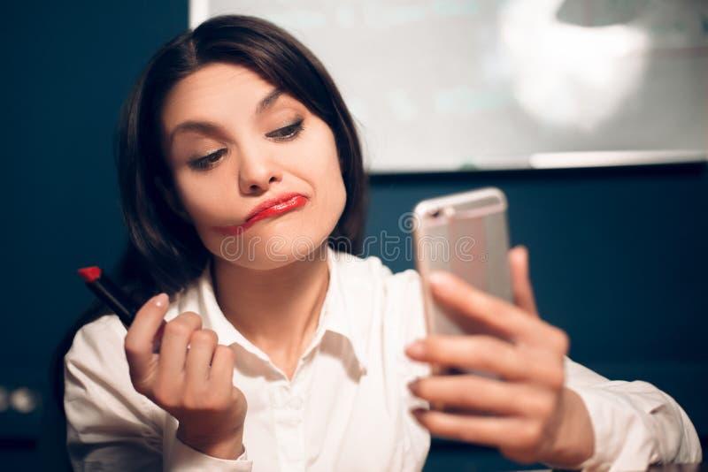 Galen gladlynt kvinna som applicerar läppstift royaltyfria bilder