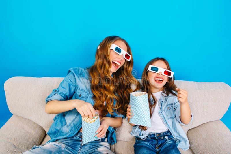 Galen gyckel av den glade modern med den roliga dottern i exponeringsglas 3D på soffan som äter popcorn på blå bakgrund B?rande j arkivfoto