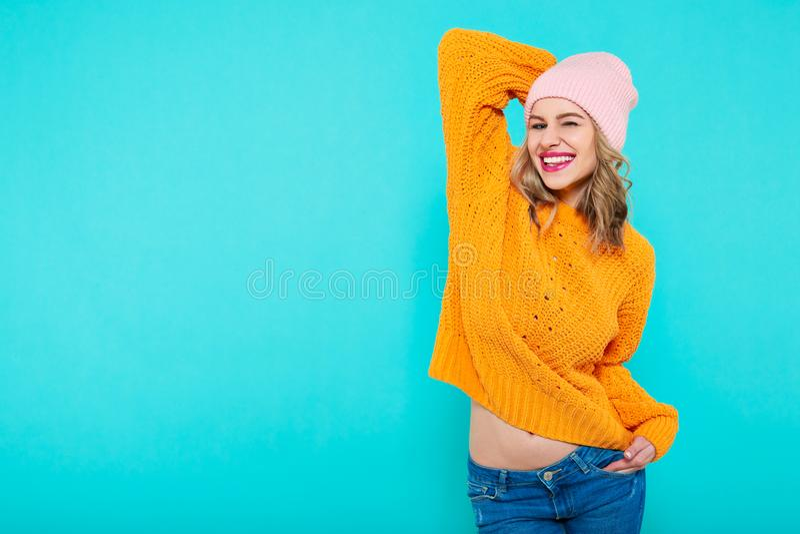 Galen härlig moderiktig flicka med uppnosigt leende i färgrik kläder och rosa beaniehatt Attraktiv kall stående för ung kvinna arkivfoton
