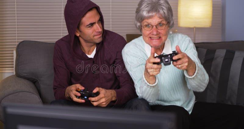 Galen mormor som slår hennes sonson på videogames royaltyfria foton