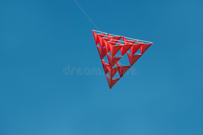 Galen röd tetrahedral drake med blå himmel royaltyfria bilder